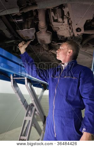 Mechanic repairing with a spanner the below of a car in a garage