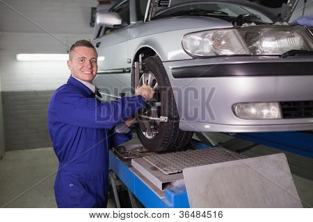 Smiling mechanic standing while repairing a car wheel in a garage