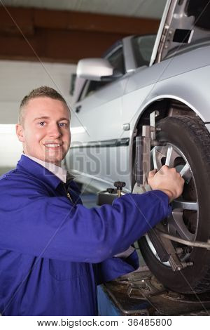 Smiling mechanic repairing a car wheel in a garage