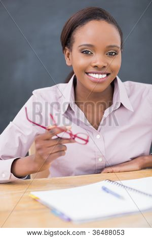 Teacher holding glasses while smiling in a classroom