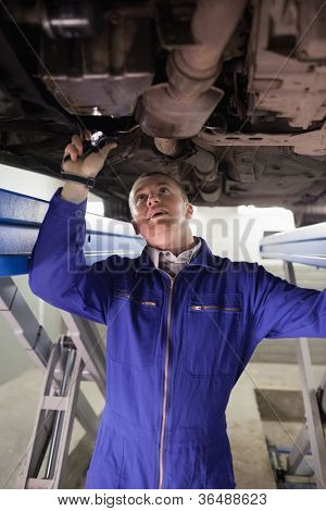 Mechanic illuminating a car with a flashlight in a garage