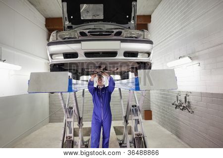 Mechanic standing while repairing a car with tools in a garage