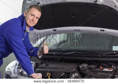 Mechanic looking at camera with his thumb up in a garage