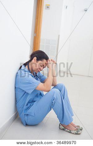 Enfermeira triste sentado no chão na enfermaria do hospital
