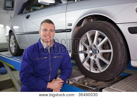 Man looking at camera next to a car in a garage
