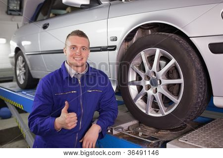 Man looking at camera next to a car with his thumb up in a garage
