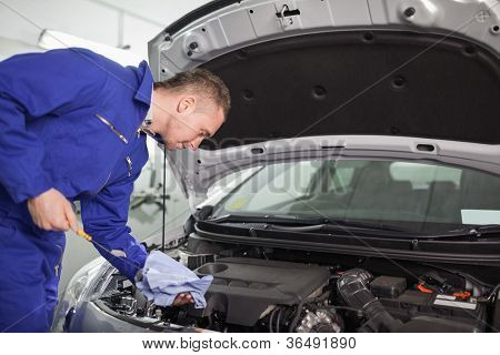 Mechanic looking at a dipstick while holding it in a garage