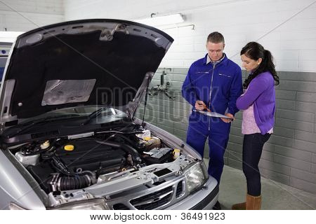 Mechanic holding a clipboard next to a woman in a garage