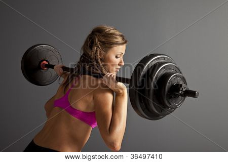 Attractive young woman with barbells on shoulder
