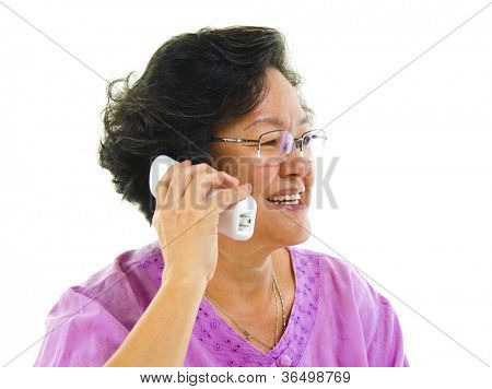 Happy mature Asian woman talking on phone, isolated on white background