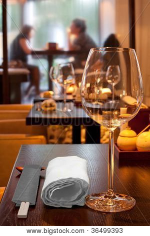 table with glasses, towel, sticks in sushi bar, couple sitting by window