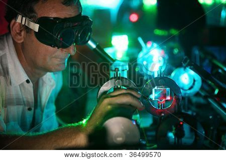 Scientist  in laser vision glasses engaged in research in his lab show movement of microparticles by laser