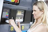 pic of gasoline station  - Mid adult woman pays for gasoline at the station - JPG