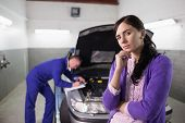 Thoughtful woman next to a mechanic in a garage
