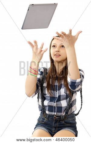 The girl throws in the air tablet PC .  Teenage girl in a plaid shirt and short denim shorts, tosses