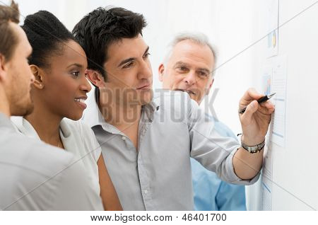 Group Of Business People Analyzing Graphs and Charts in Office