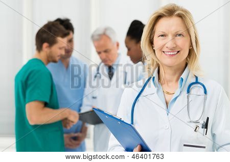 Happy Female Doctor Standing In Front Of Her Co-worker