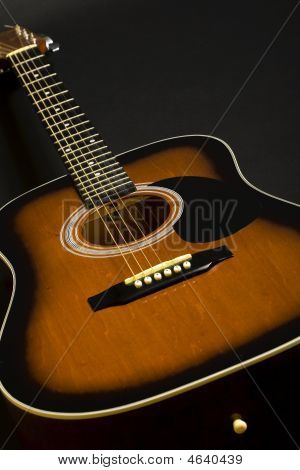 Closeup Of An Acoustical Guitar On Black