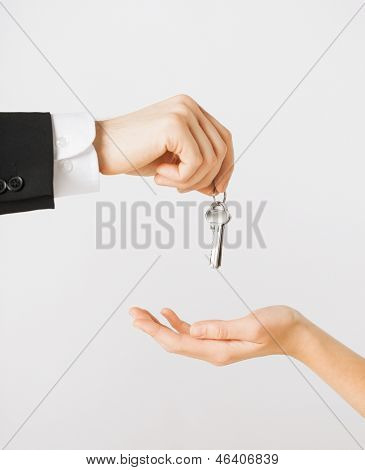 picture of man hand passing house keys to woman