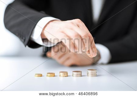 picture of man putting stack of coins into one row