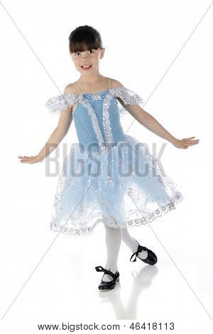 A happy young girl tap dancing in a beautiful blue and silver dress.  On a white background.