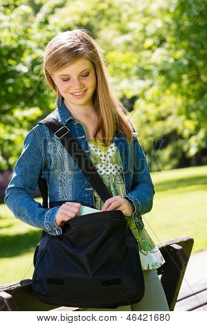 Happy student girl with bag standing outside in the park