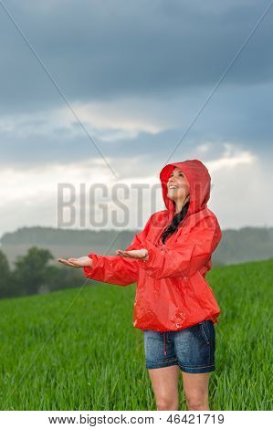 Carefree young girl enjoying rainy weather in raincoat