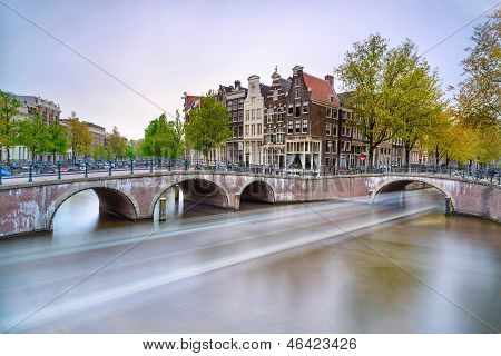 Amsterdam. Bridge And Water Canal. Boat Light Trail On Sunset. Holland Or Netherlands.