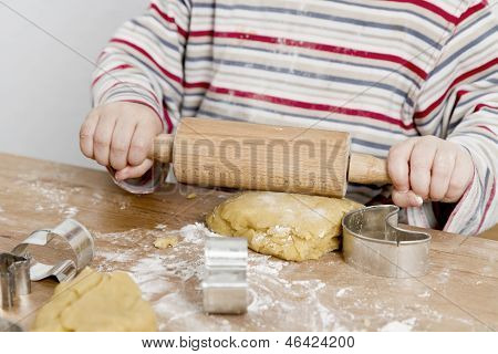 Child Rolling Dough On Wooden Desk