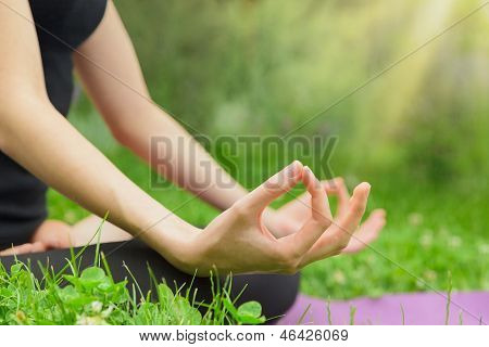 Woman Meditating In The Lotus Position Close Up