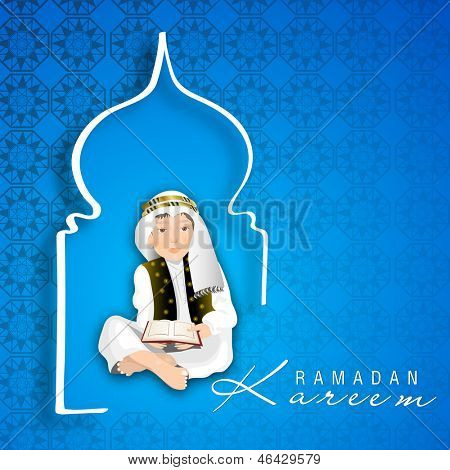Muslim boy reading Islamic religious holy book on blue background for Ramadan Kareem.