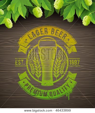 Beer emblem painted on wooden surface and ripe hops and leaves - vector illustration