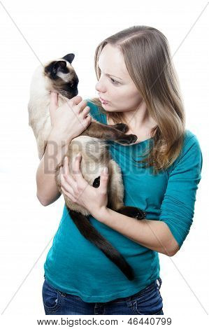young woman scolding her siamese cat