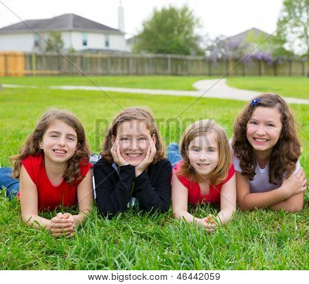 Children girls group lying on lawn grass smiling happy together in a row