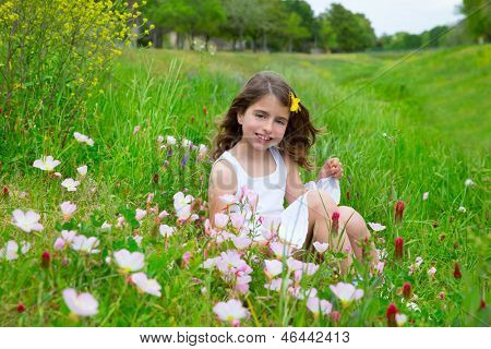 beautiful children girl on spring meadow with poppy flowers