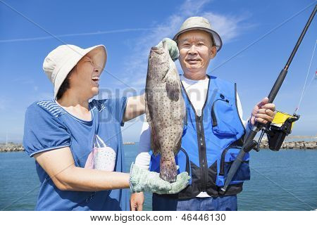 Happy Asian Senior Couple Fishing And Showing Big Grouper
