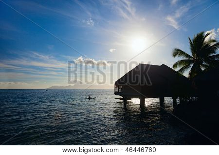 Silhouette of overwater bungalow at sunset