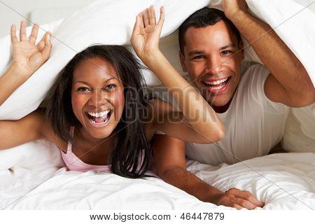 Paar erholsame Bett versteckt unter der Bettdecke