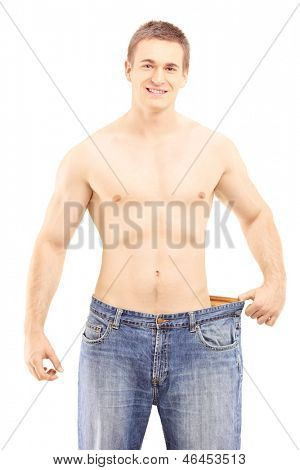 Shirtless smiling male showing his lost weight by putting on an old jeans, isolated on white background