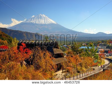 Historic Japanese huts in Kawaguchi, Japan with Mt Fuji Visible in the distance.