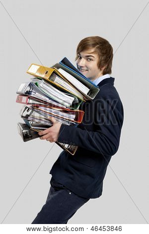 Young business man carrying a bunch of folders