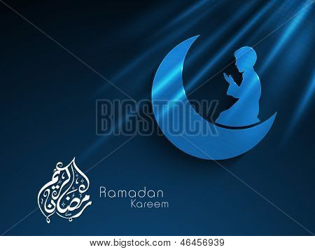 Arabic Islamic calligraphy of text Ramadan Kareem with Muslim boy in traditional dress praying on moon on blue background for Ramadan Kareem.