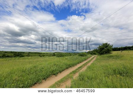 rut road among steppe in nice cloudy day