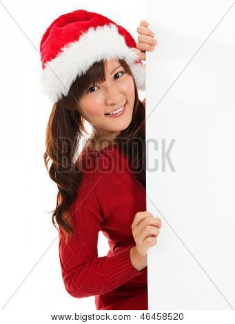 Christmas girl peeking from behind blank sign billboard. Advertising photo of young smiling Santa woman in Santa hat showing paper sign. Asian Chinese female model isolated on white background