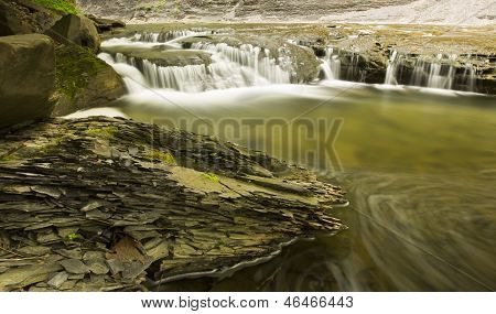 Time Lapse Stream With A Chunk Of Brittle Shale Rock In The Foreground