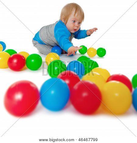 Komische Kind spielen mit bunten Plastikbällen