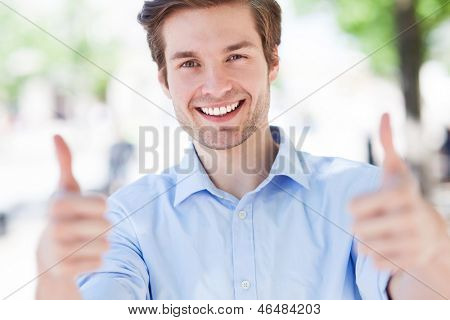 Young man showing thumbs up