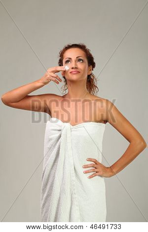 Beautiful middleaged caucasian woman with cream on her face
