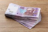 pic of payday  - Ukrainian money on wooden background - JPG