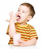 pic of finger-licking  - Cute little boy with a glass of milk licking his finger - JPG